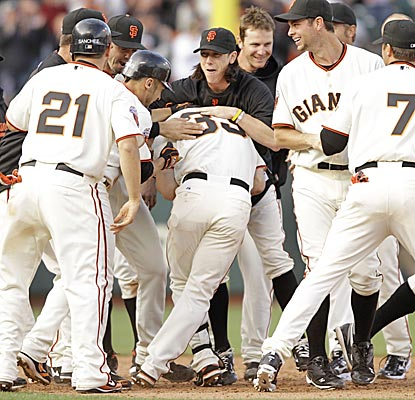 Aaron Rowand is mobbed by his Giants teammates near second base after driving in the game-winning run in the 12th inning. (AP)