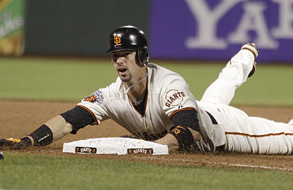 Aaron Rowand slides in safely at third base for a triple before scoring the tiebreaking run for San Francisco. (AP)