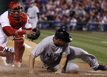 Gaby Sanchez avoids the tag to score on a two-RBI single from Greg Dobbs as the Marlins beat the Phillies. (AP)