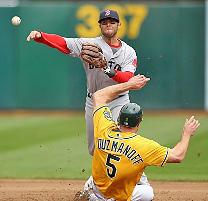 Dustin Pedroia tries to turn a double play during a  win in Oakland that turns around the Red Sox woes on the road.  (Getty Images)