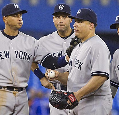 Yankees pitcher Bartolo Colon gets a pat on the back from his teammates after going 6 2/3 innings in the Yankees' win.  (AP)