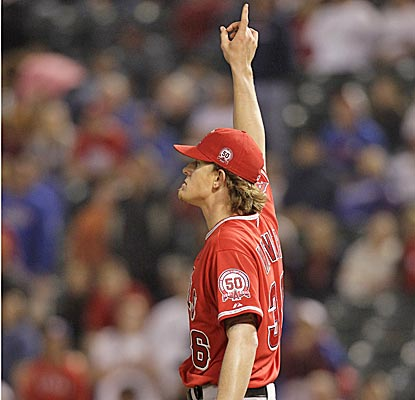 Angels starter Jered Weaver points skyward at a pop-up for the final out in the ninth to earn his fifth win of the season. (AP)