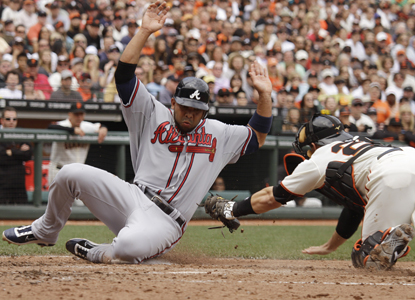 Alex Gonzalez slides safely across home plate on a fielder's choice in the seventh inning of the Braves' win over the Giants. (AP)