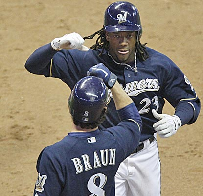 The Brewers' Ryan Braun congratulates Rickie Weeks after Weeks' home run in the eighth inning. (AP)