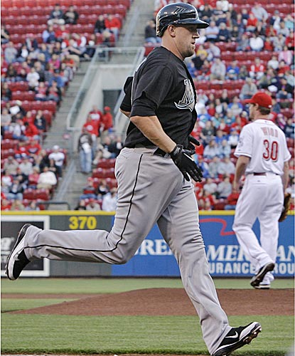 The Marlins' John Buck rounds the bases after blasting a three-run homer off Reds starter Travis Wood in the first inning. (AP)