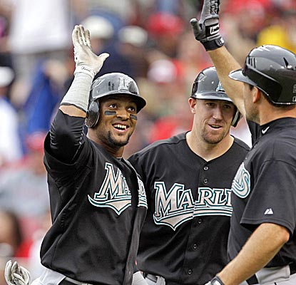 The Marlins' Emilio Bonifacio is congratulated by John Buck and Greg Dobbs (right) after hitting a three-run homer. (AP)