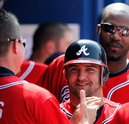 The Braves' Dan Uggla is congratulated by Chipper Jones after scoring in the seventh inning. (Getty Images)