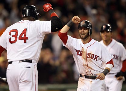 Dustin Pedroia (right) celebrates scoring a crucial run in the seventh on an Adrian Gonzalez RBI single.  (Getty Images)