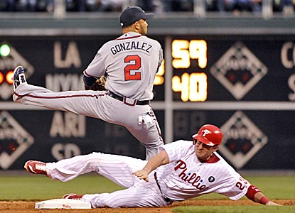 Braves shortstop Alex Gonzalez avoids the slide of the Phillies' Brian Schneider during the second inning. (US Presswire)