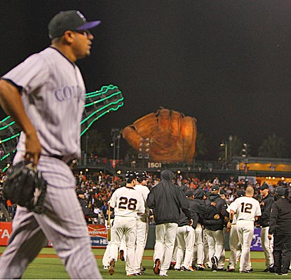 The Giants celebrate in front of Rockies relief pitcher Franklin Morales after Mike Fontenot's game-winning RBI.   (US Presswire)