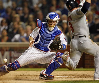 Nick Punto evades Cubs catcher Koyie Hill to score a run in the seventh inning.  (US Presswire)