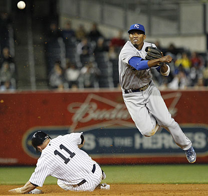 Royals SS Alcides Escobar turns a double play in the eighth, forcing out Brett Gardner (11). (AP)