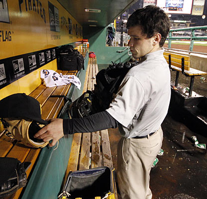 A clubhouse attendant gathers gloves and hats after the Dodgers-Pirates game is called off.  (AP)