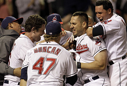 Travis Hafner is mobbed by teammates after his two-run homer with two outs in the ninth inning. (AP)