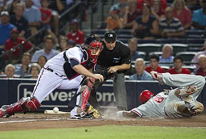 Ryan Howard slides in safely when catcher Brian McCann is unable to collect a short-hop throw to the plate. (US Presswire)