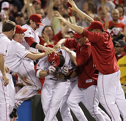 Reds players jump all over Joey Votto, who drives in the winning run off reliever Jason Motte. (AP)