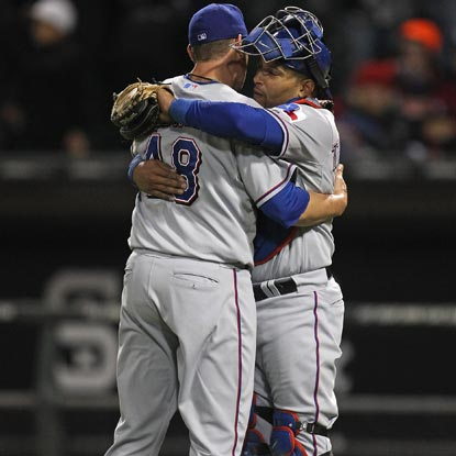 The Rangers' Colby Lewis (left) is congratulated by Yorvit Torrealba after striking out seven in his first career shutout. (Getty Images)