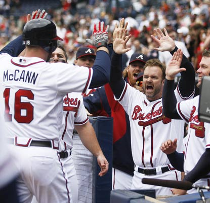 Brian McCann is enthusiastically welcomed back after his pinch-hit homer ties it. His 11th-inning shot wins it.  (US Presswire)