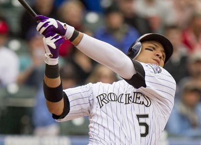 Carlos Gonzalez swings through a two-run single to cap a four-run eighth-inning rally for the Rockies.  (Getty Images)