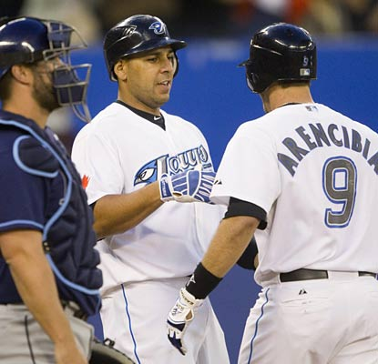 Juan Rivera greets J.P. Arencibia after the latter's two-run blast gives the Blue Jays the lead for good. (AP)