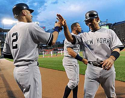 Derek Jeter congratulates Jorge Posada (right) after scoring. Posada started at first base for the first time since 2008. (Getty Images)