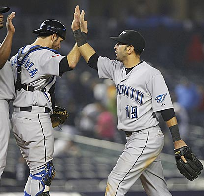 J.P. Arencibia (left) and Jose Bautista, who deliver big hits for Toronto, congratulate each other after winning in the Bronx.  (AP)