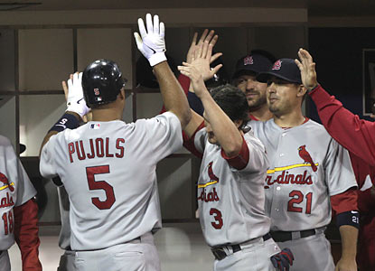 Albert Pujols gets a warm greeting in the Cards dugout after hitting his first home run in 106 at-bats. (AP)