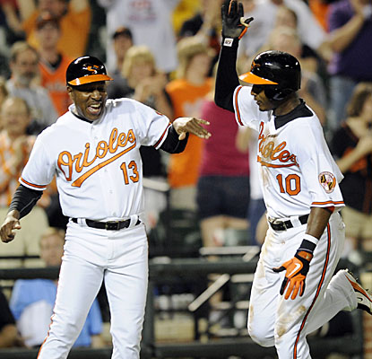 Adam Jones (right) celebrates his two-run walk-off homer with Orioles 3B coach Willie Randolph. (AP)