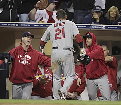 Mark McGwire (left) leads the welcoming committee for Allen Craig after he scores the winning run in the 11th inning.  (AP)