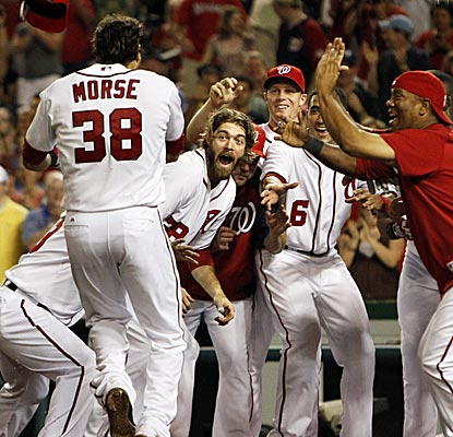 The Nationals wait for walk-off hero Michael Morse to cross home plate in the ninth inning.  (AP)