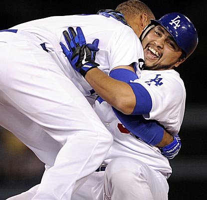 Dioner Navarro is tackled by Matt Kemp after the Dodgers catcher hits a single through a five-man infield to beat the Marlins.  (AP)