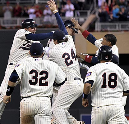 The Twins mob Danny Valencia after his bases-loaded single wins the game in the bottom of the 10th.  (AP)