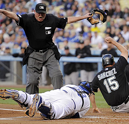 Gaby Sanchez is safe at home for the Marlins in a wild day at the ballpark in Los Angeles.  (AP)