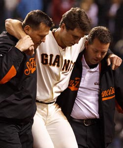 Buster posey is helped off the field after breaking his leg on a vicious hit at the plate by Scott Cousins. (US Presswire)