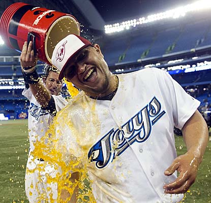 Jo-Jo Reyes gets an orange shower courtesy of Jays catcher J.P. Arencibia after getting his first win in 29 starts. (AP)