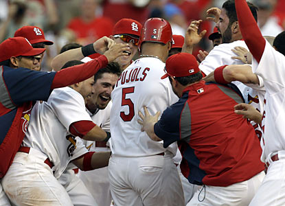 Albert Pujols is mobbed by teammates after hitting a walk-off homer in the 12th -- his second blast in the game. (AP)