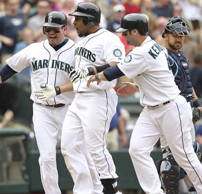 Miguel Olivo and the Mariners are in a joyous mood after his three-run shot caps a four-run eighth inning.  (Getty Images)