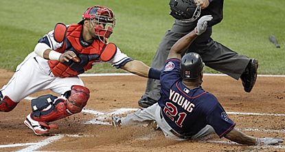 Minnesota's Delmon Young beats Carlos Santana's tag to score in the second inning on Matt Tolbert's two-run single.  (AP)