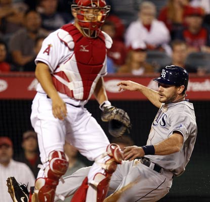 John Jason slides in safely after Reid Brignac lays down the squeeze bunt in the 10th inning.  (AP)