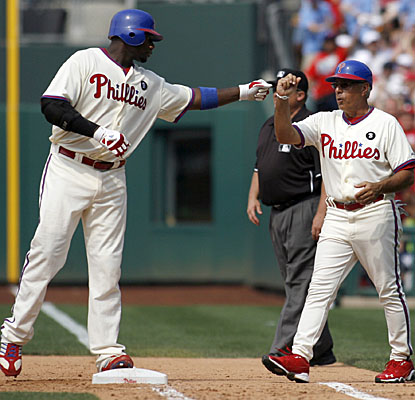 Ryan Howard gets an attaboy from first base coach Sam Perlozzo after he hit a two-run RBI single in the seventh. (AP)