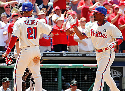 Wilson Valdez and Jimmy Rollins score in a six-run third inning against Elih Villanueva in his big-league debut.  (Getty Images)