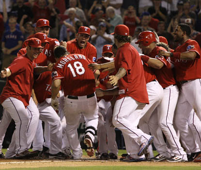 Mitch Moreland is mobbed by teammates as his upper-deck home run seals the Rangers' victory over Houston. (AP)