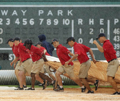 Fenway's grounds crew has a busy day -- the game is delayed four times before getting called. (AP)