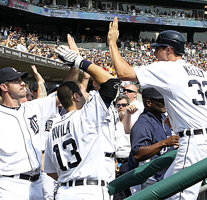 The Tigers celebrate in the dugout after Don Kelly scores on a Miguel Cabrera single in Detroit's big eighth inning. (Getty Images)