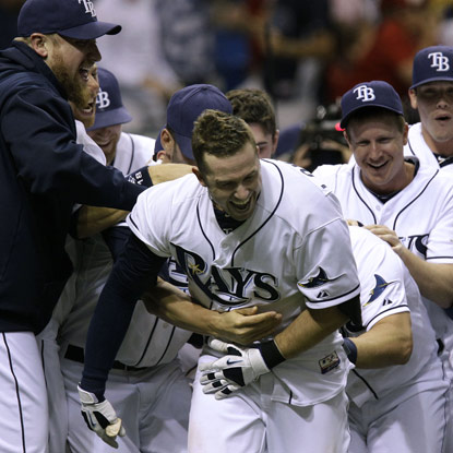 Evan Longoria (center) is swarmed by 'mates after sending an 0-1 pitch into the left-field seats in the bottom of the ninth.  (Getty Images)