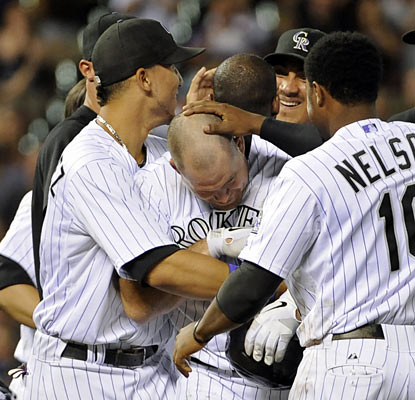 Ty Wigginton gets a proper greeting after he delivers the Rockies' game-ending hit with two outs in the 13th inning.  (AP)