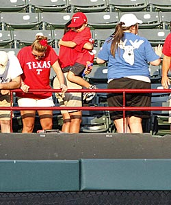 Fans look over the outfield railing after Rangers fan Shannon Stone fell while trying to grab a tossed ball. (AP)