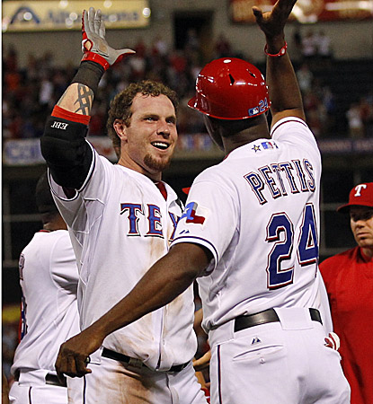 Rangers first base coach Gary Pettis congratulates Josh Hamilton following Hamilton's walk-off home run against the A's. (US Presswire)