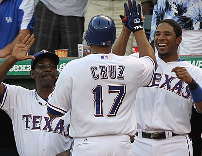 Skipper Ron Washington and Elvis Andrus cheer Nelson Cruz in the dugout after Cruz's three-run homer. (Getty Images)