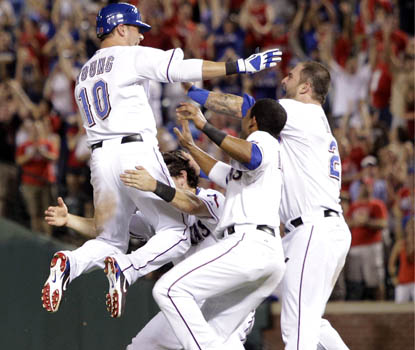 Michael Young leaps into the arms of his teammates after his ninth-inning hit lifts Texas to a win over Toronto. (AP)